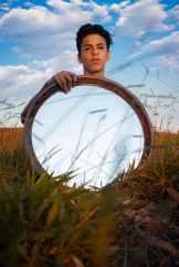 man holding a mirror standing on green grass field